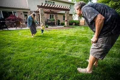 family playing in healthy lawn with no crabgrass
