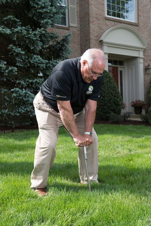 Oasis lawn care technician testing soil