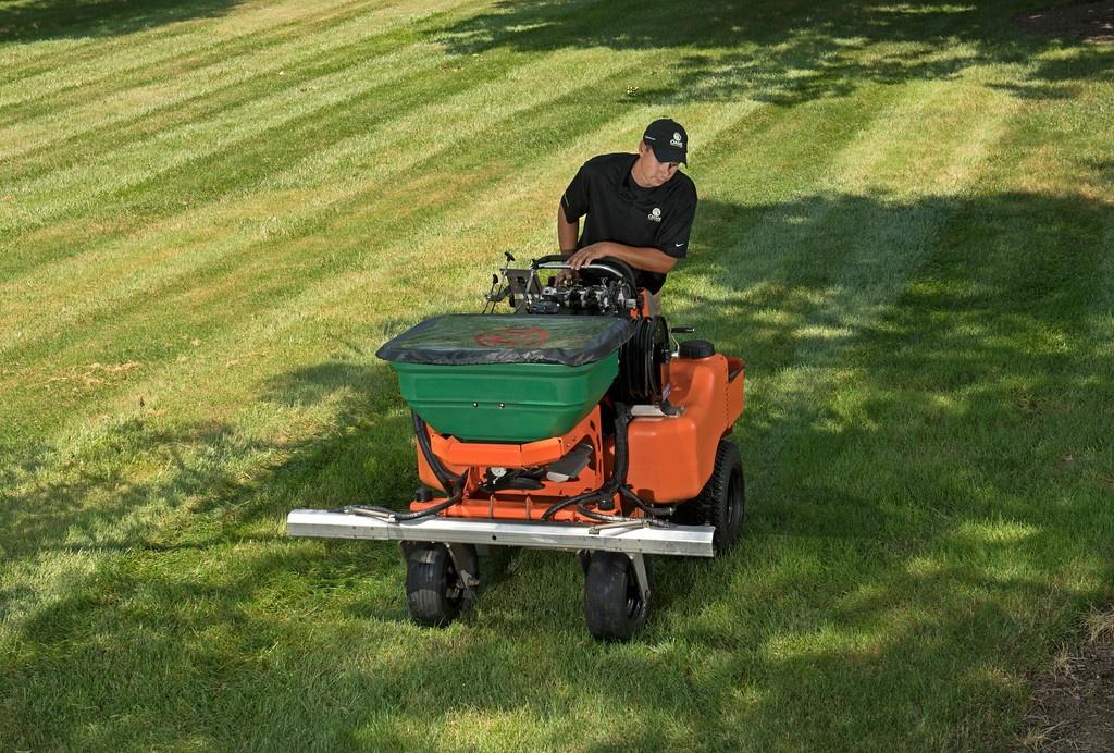 lawn care tech applying fertilizer