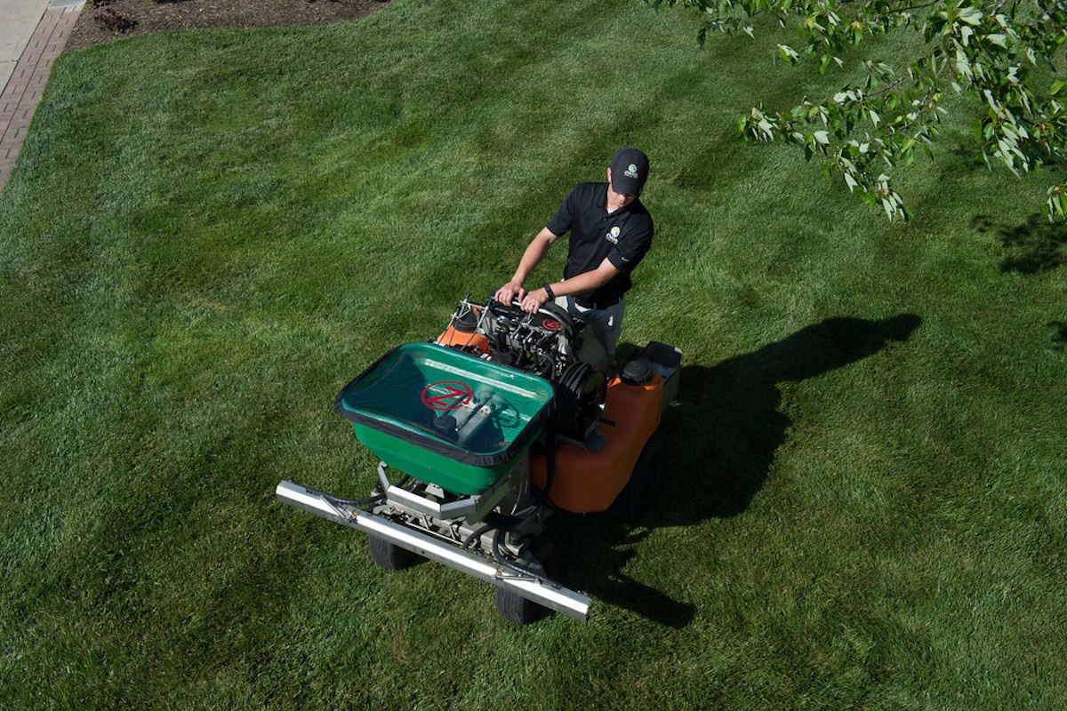 lawn technician spraying to kill weeds in spring in Ohio