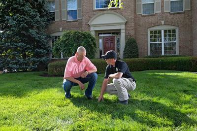 lawn technician educating customer in lawn