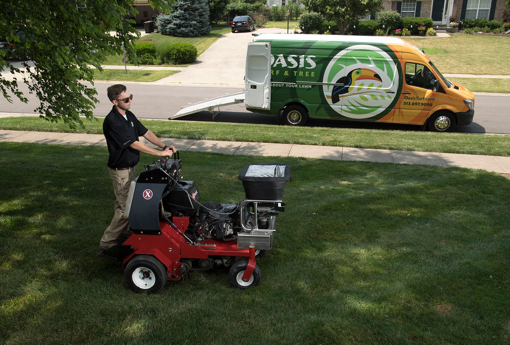 Oasis lawn care technician aerating lawn