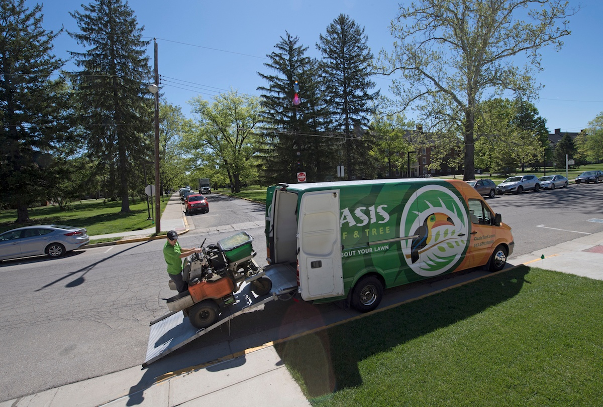 Lawn care technician unloading equipment