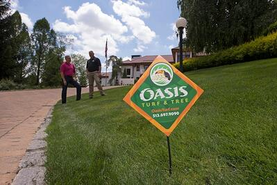 Oasis Turf & Tree lawn care sign in lawn treated with biostimulants