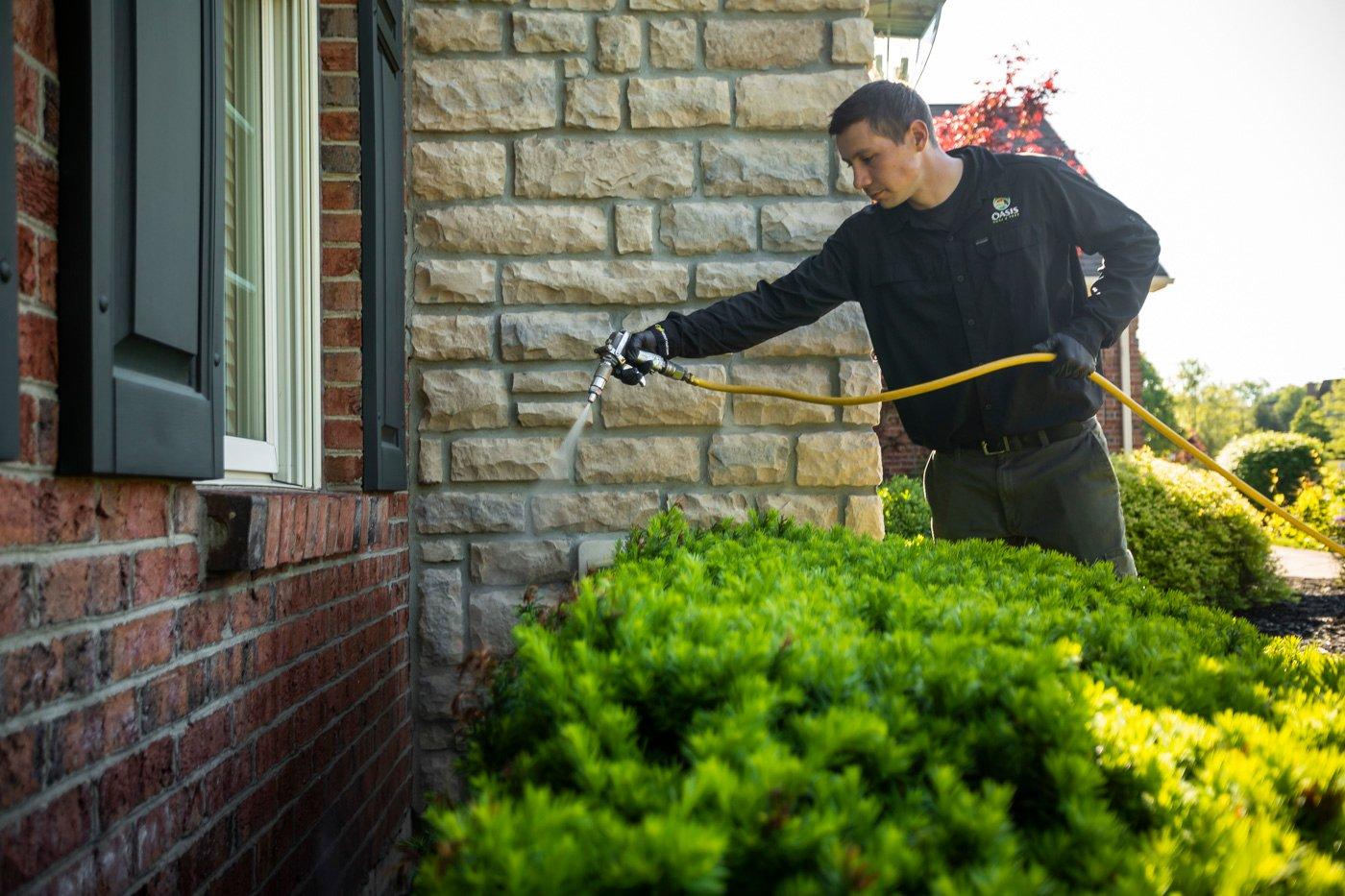 Perimeter pest control technician spraying home in Cincinnati