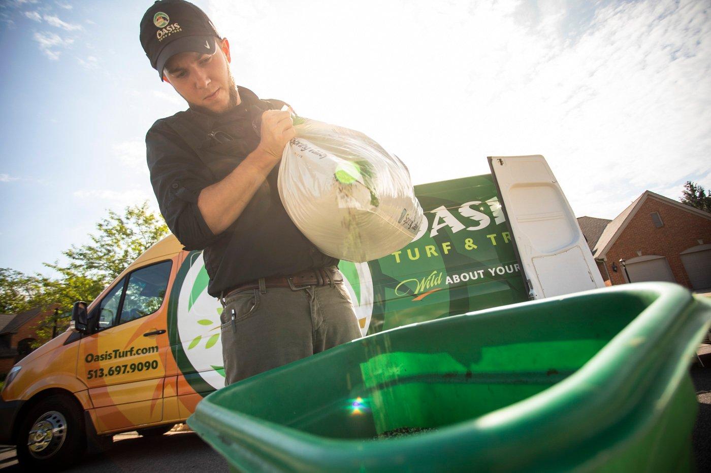 Lawn care technician pouring fertilizer into spreader
