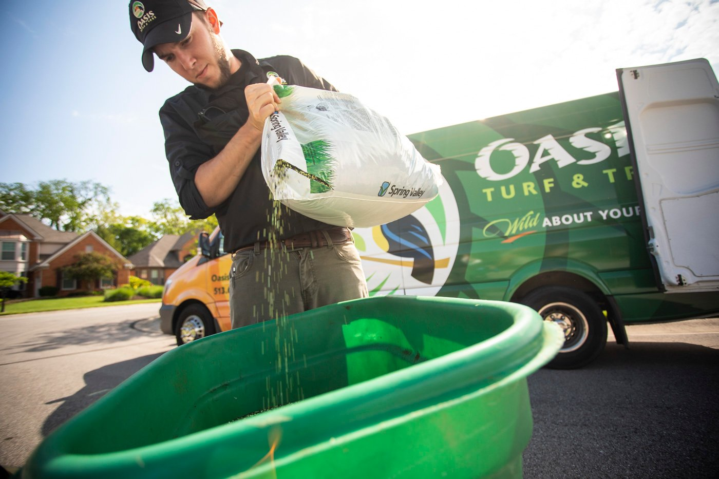 Oasis technician preparing fertilizer to be spread on a lawn