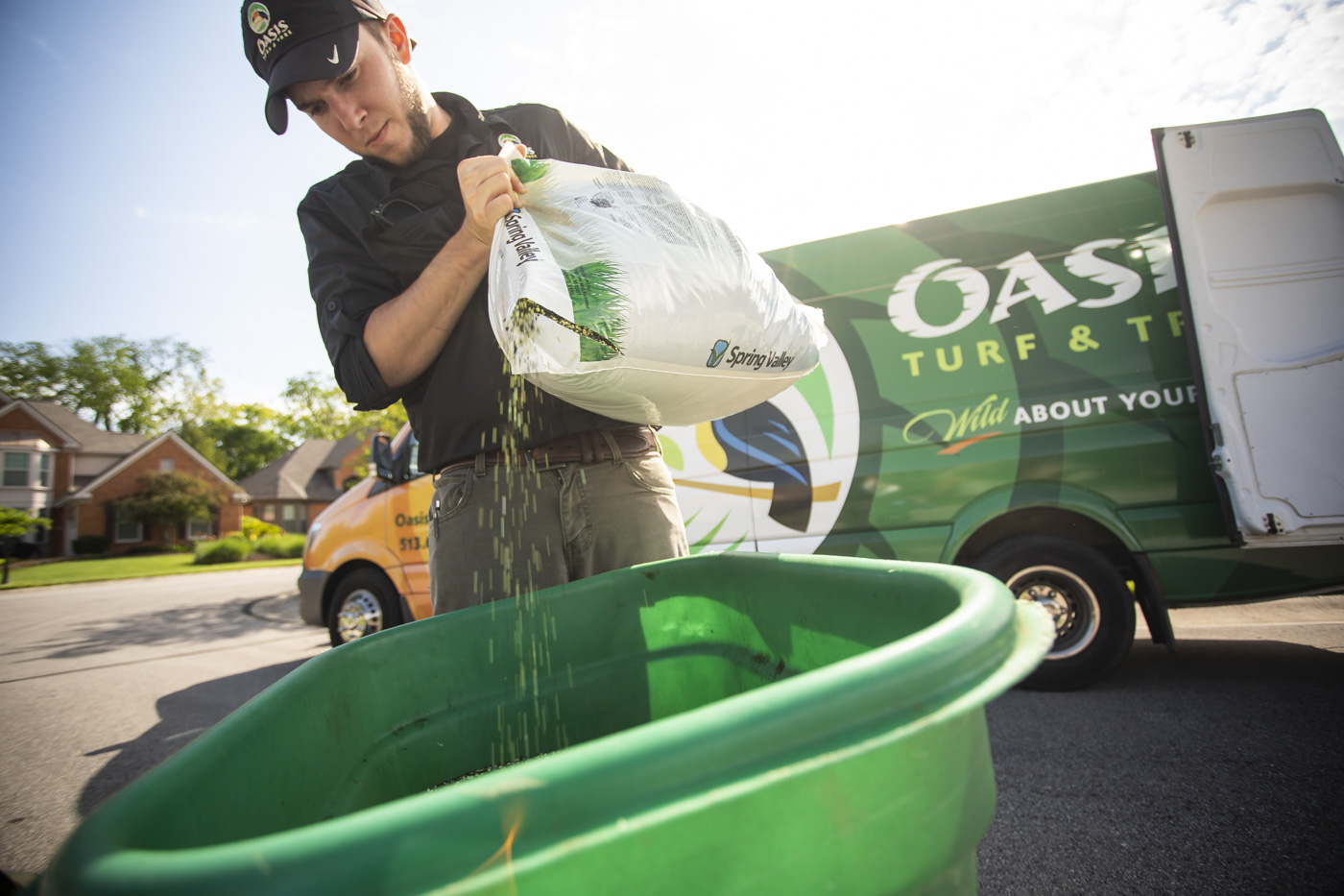 Lawn care technician prepping fertilizer to be applied to a lawn