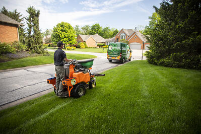 Oasis lawn care technician fertilizing lawn in Cincinnati