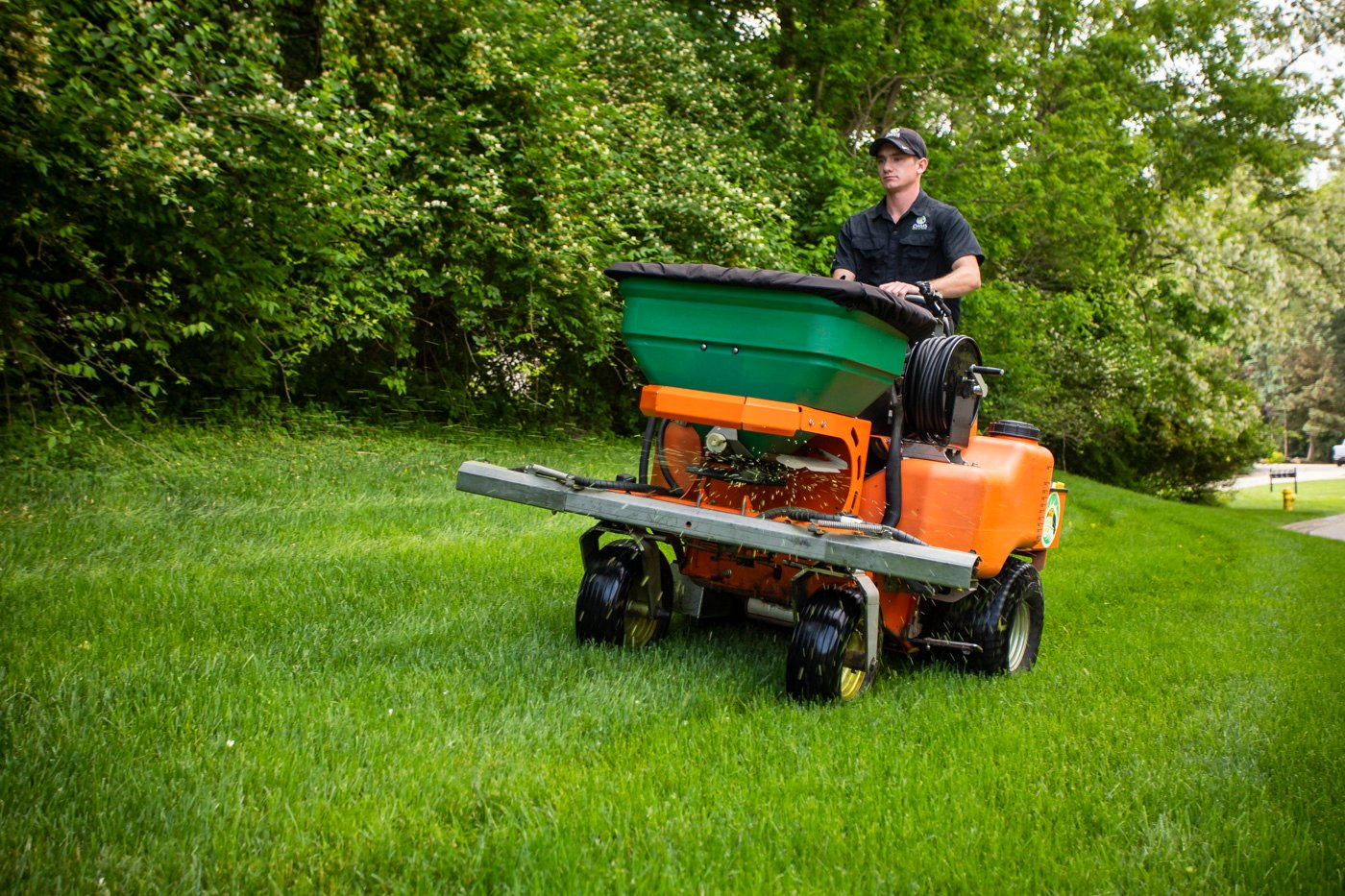 Oasis Lawn Care technician applying granular fertilizer with top-quality equipment