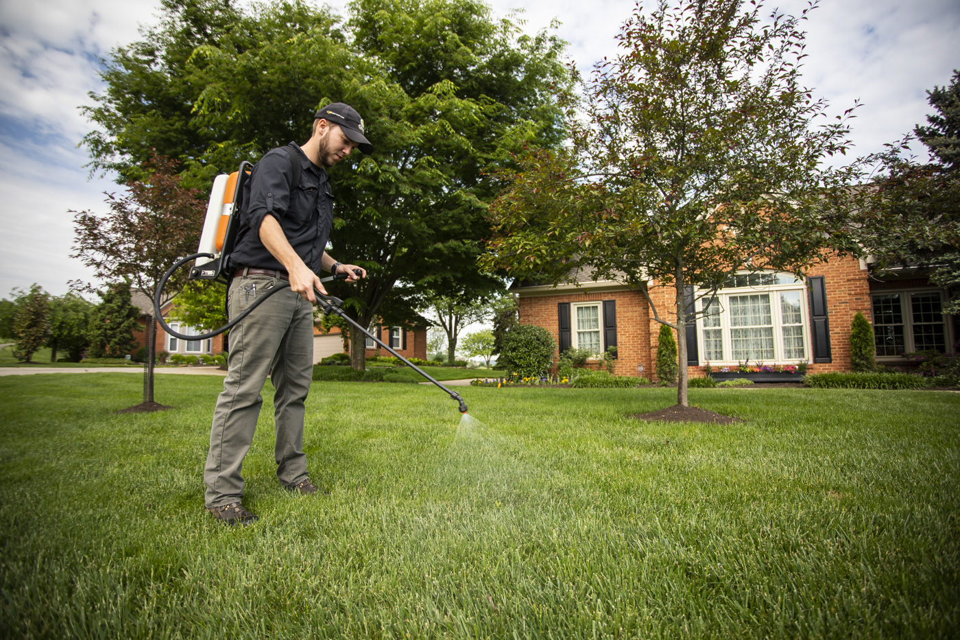 Lawn care technician spraying lawn in Cincinnati