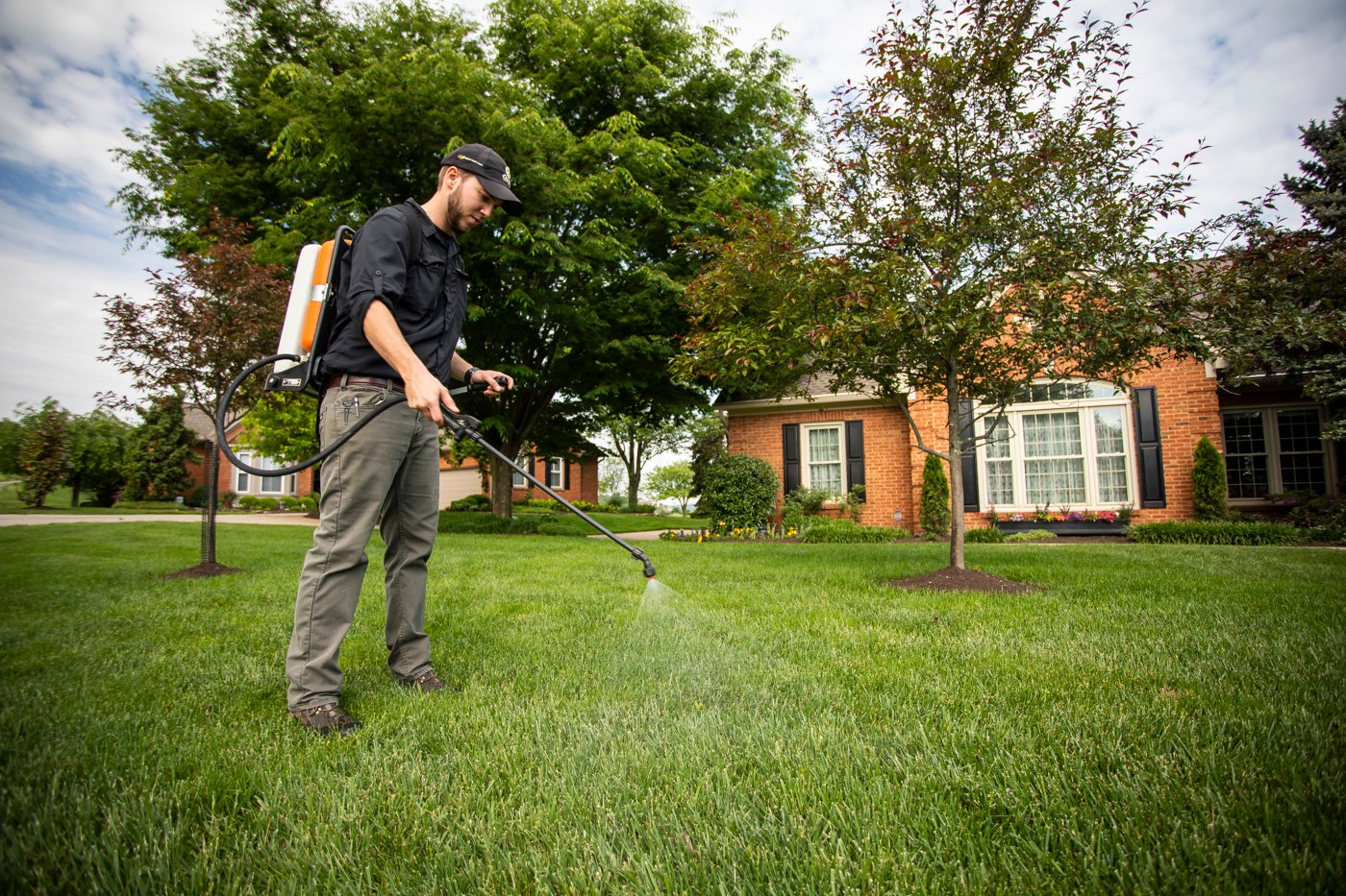 Lawn care technician spraying for weeds