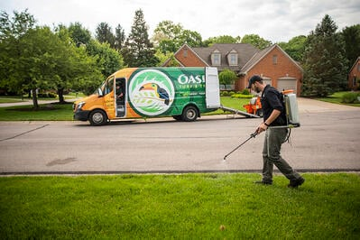 Oasis lawn care technician spraying lawn