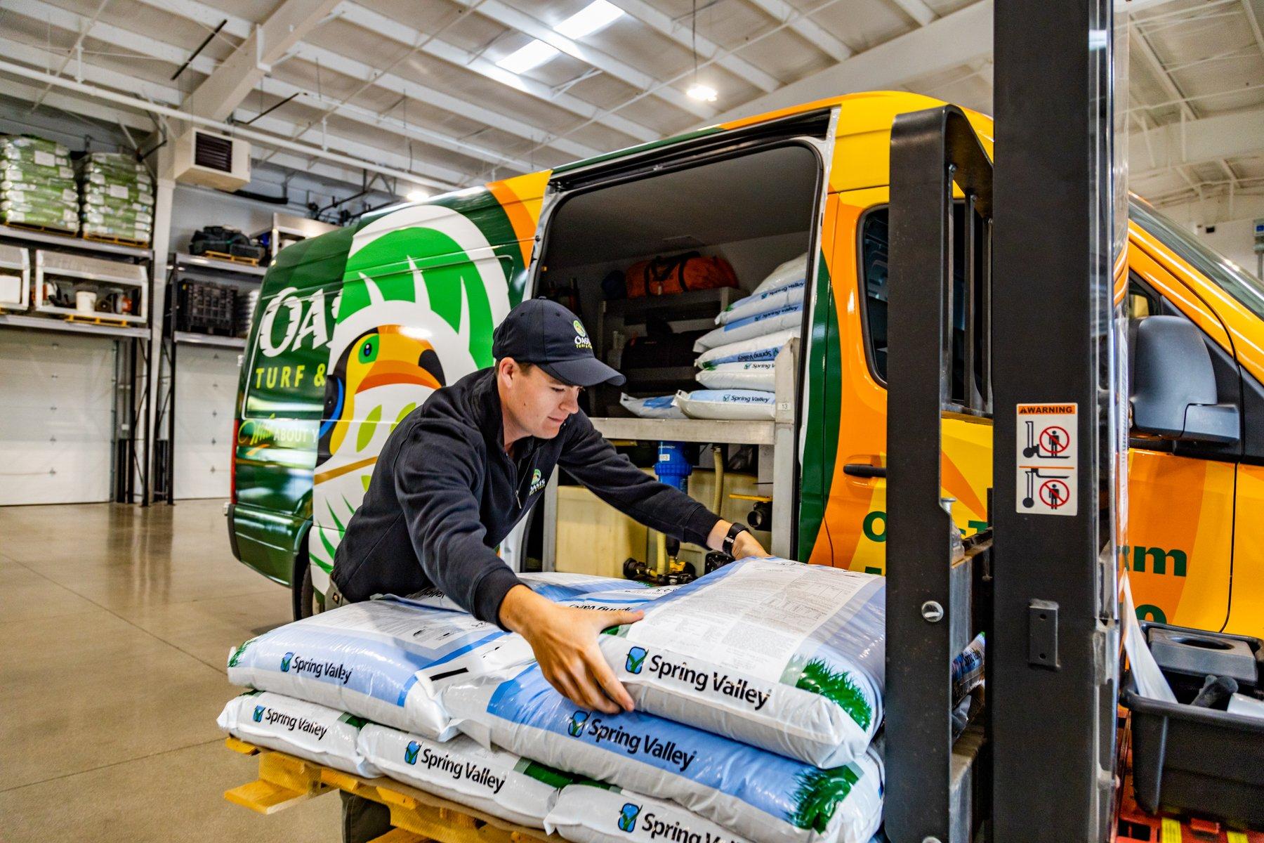 Oasis crew using forklift to load fertilizer into van