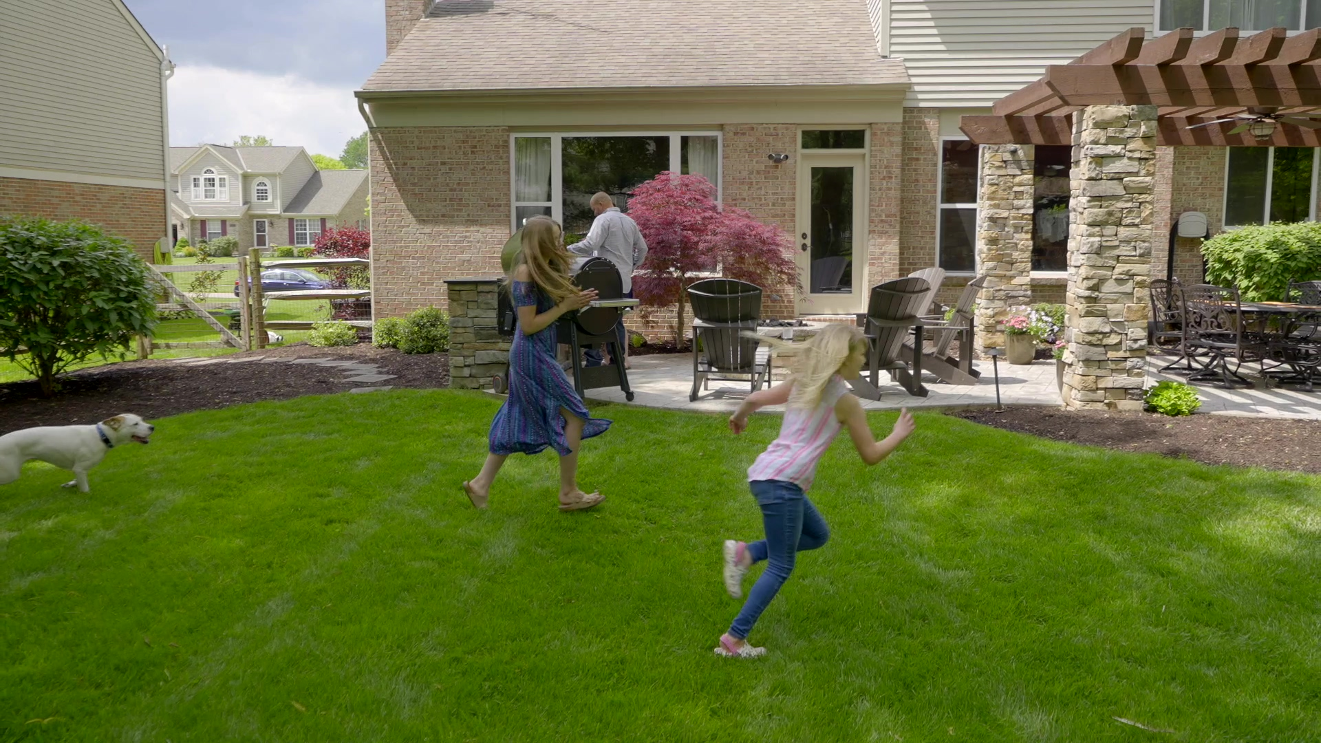 Kids playing in their yard with their dog